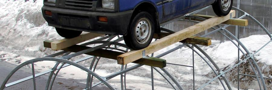 Прочная конструкция теплицы. Автомобиль на крыше теплицы.
